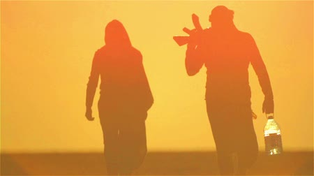 Arab refugees man and woman at sunset, with arms. Muslim couple in the desert with guns and a bottle of water. Wideo