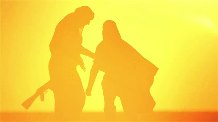 Arab refugees man and woman at sunset, with arms. Muslim couple in the desert with guns and a bottle of water. 影像素材