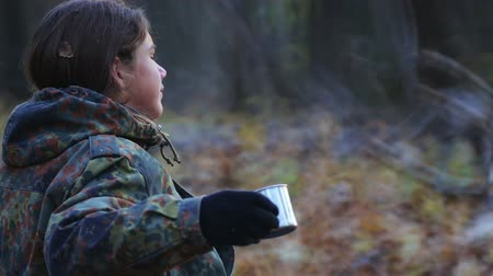 Boy drinking tea in the autumn forest. Teen scout drinks tea in the park for a walk.