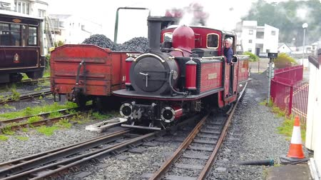 viktoriánus : Portmadog, Wales - June 15th 2019: Slow motion of a Ffestiniog railway steam train leaving from Porthmadog station Stock mozgókép