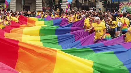LONDON, UK - July 6th 2019: People hold a huge LGBTQ gay pride rainbow flag at the start of the London pride event