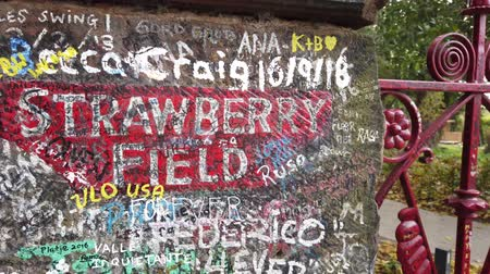 навсегда : Liverpool, UK - October 31 2019: Iconic red gateway to Strawberry fields in Liverpool. Made famous by The Beatles song Strawberry fields forever. Стоковые видеозаписи
