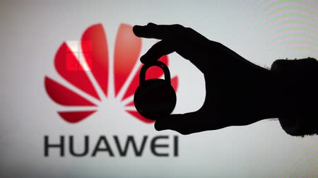 destravar : LONDON, UK - January 29th 2020: Huawei security issues. Silhouette of a hand holding a padlock in front of the Huawei logo.