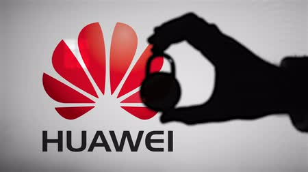 щит : LONDON, UK - January 29th 2020: Huawei security issues. Silhouette of a hand holding a padlock in front of the Huawei logo.