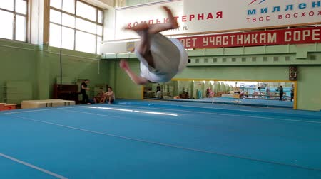 gymnasta : IZHEVSK, RUSSIA - MART 2014: Aerial view of gymnast extremely Jumping front flip from the balcony. Acrobat man practicing his skills at the gym