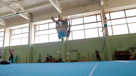 gymnasta : IZHEVSK, RUSSIA - MART 2014: Three Axis Gimbal stabilized Gymnast doing frontflip and backflip. Acrobat man practicing his skills at the gym