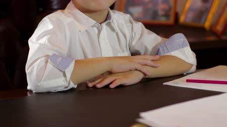 boyish : Young kid concentrated sitting at the table
