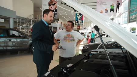 revendedor : IZHEVSK, RUSSIA - JUNE 22, 2014: Salesman in car dealership showing customer car