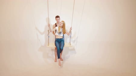architektura : Happy and attractive young couple relax on swing