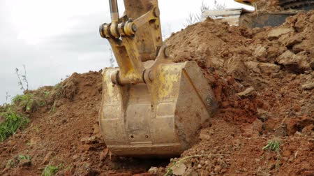 discharging : Construction Excavator Scooping and Dumping on Dirt Pile