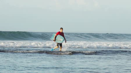 BALI, INDONESIA - OCTOBER 2017: Surfer walking in shallow water in ocean