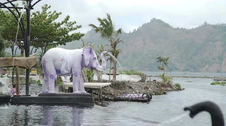 panas : Water flowing into hot springs pool from trunk of elephant statues Bali
