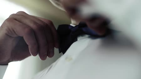 man adjusts his bowtie on a white shirt.