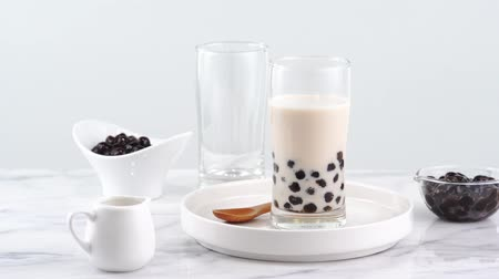 tapioca : Tasty tapioca pearl bubble milk tea in glass, popular drink in taiwan on bright marble table and white tray, homemade concept. 4K Zoom in shot video