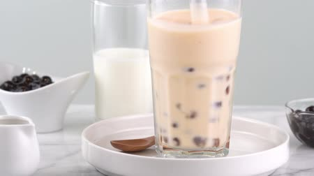 pohárek : Stirring tapioca pearl bubble milk tea in drinking glass, tasty taiwanese popular drink on bright marble table. Homemade concept. 4K shot video.