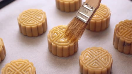 желток : Homemade cantonese moon cake before baking - Woman smearing egg on pastry with brush on baking tray for traditional festival, close up. Стоковые видеозаписи