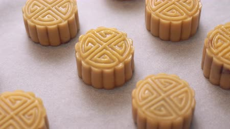 Homemade cantonese moon cake pastry on baking tray before baking for traditional festival, close up, truck left.