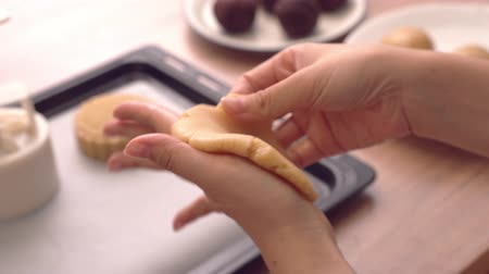 Woman making moon cake pastry with red bean paste filling wrapping by mooncake dough, festive baking for traditional Mid-Autumn festival, close up.