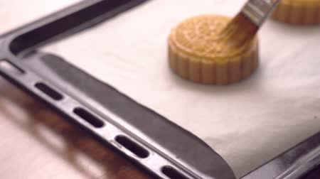 Woman smearing egg on cantonese moon cake pastry with brush befor baking on baking tray for traditional Mid-Autumn festival, close up.