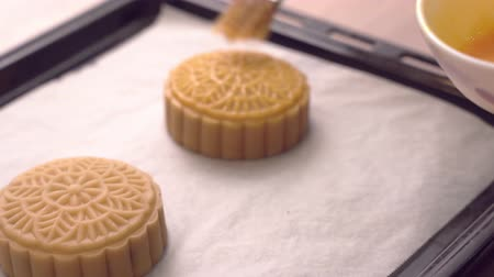 желток : Woman smearing egg on cantonese moon cake pastry with brush befor baking on baking tray for traditional Mid-Autumn festival, close up.