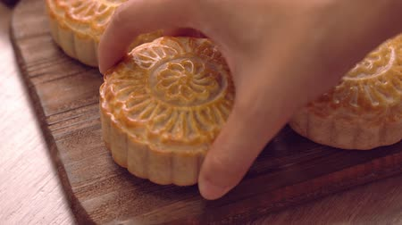 Woman putting a beautiful ready-to-eat moon cake on a wooden tray for afternoon tea, Mid-Autumn Festival custom concept, close up. Wideo