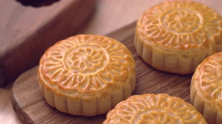 Baked cantonese moon cake pastry on a wooden tray for traditional chinese Mid-Autumn festival, close up, truck shot movement.