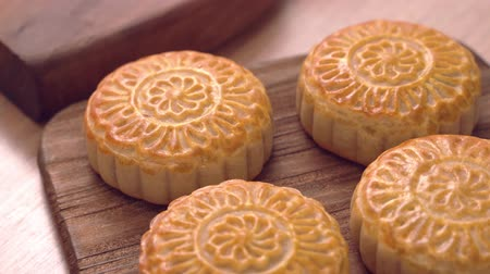 pan shot : Baked cantonese moon cake pastry on a wooden tray for traditional chinese Mid-Autumn festival, close up, truck shot movement.