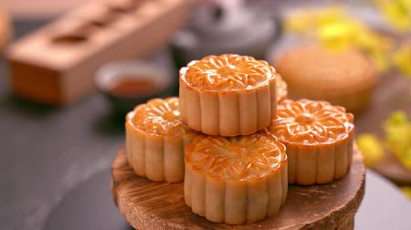 arduvaz : Beautiful Moon cakes rotating on a wooden tray with tea and flower on black slate background. Chinese traditional Mid-Autumn Festival concept video.