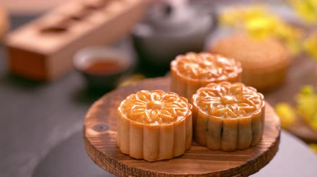 demlik : Woman taking beautiful moon cake pastry to eat and share with family to celebrate Mid-Autumn Festival. Reunion event concept.