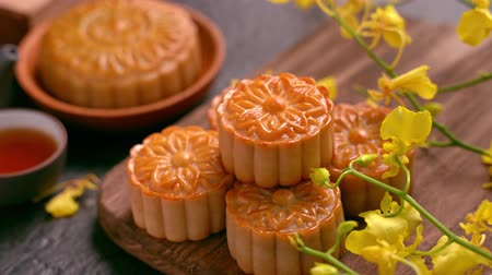 arduvaz : Beautiful Moon cakes on a wooden tray with tea and flower on black slate background. Chinese traditional Mid-Autumn Festival concept. Truck right.
