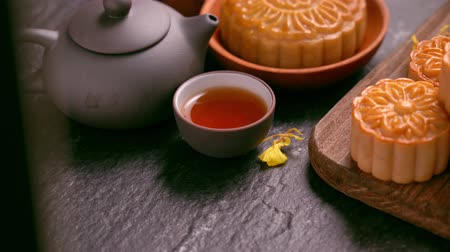 Beautiful Moon cakes on a wooden tray with tea and flower on black slate background. Chinese traditional Mid-Autumn Festival concept. Truck right.
