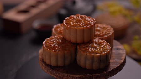 fade in : Beautiful Moon cakes on a wooden tray with tea and flower on black slate background. Chinese traditional Mid-Autumn Festival concept, fade in. Stock Footage