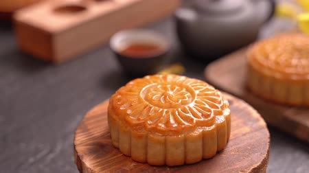 Woman putting beautiful moon cake pastry on table to eat to celebrate Mid-Autumn Festival. Event Service concept.