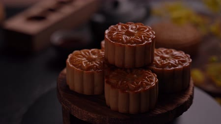 slate : Beautiful Moon cakes on a wooden tray with tea and flower on black slate background. Chinese traditional Mid-Autumn Festival concept, fade in. Stock Footage