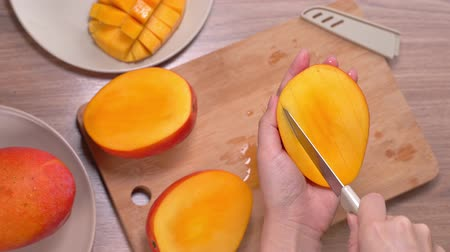 Young woman is cutting a beautiful fresh juicy mango to eat on a wooden table and chopping board in the kitchen, close up , 4K video shot.