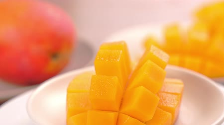 turn table : Beautiful fresh chopped mango, showing on a rotating white plate, close up, 4K video shot.