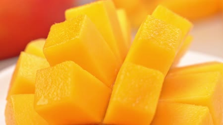Beautiful fresh chopped mango, showing on a rotating white plate, close up, 4K video shot.