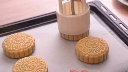 Process of making moon cake for Mid-Autumn Festival - Molding shape of moon cake pastry on baking tray. Woman festive homemade concept, close up. Wideo