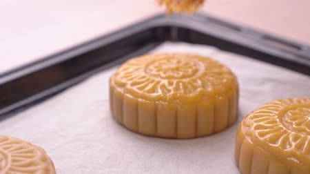 Process of making moon cake for Mid-Autumn Festival - Woman brushing egg liquid on pastry surface before baking. Festive homemade concept, close up. Wideo