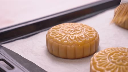 желток : Process of making moon cake for Mid-Autumn Festival - Woman brushing egg liquid on pastry surface before baking. Festive homemade concept, close up. Стоковые видеозаписи