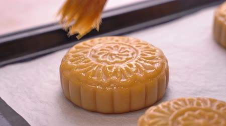 chefs table : Process of making moon cake for Mid-Autumn Festival - Woman brushing egg liquid on pastry surface before baking. Festive homemade concept, close up. Stock Footage