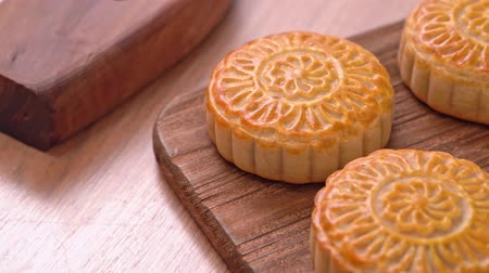 Fresh baked Chinese moon cake pastry on wooden serving tray for traditional Mid-Autumn festival, close up, truck shot movement. 4K Resolution.