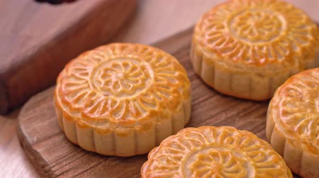 pan shot : Fresh baked Chinese moon cake pastry on wooden serving tray for traditional Mid-Autumn festival, close up, truck shot movement. 4K Resolution.