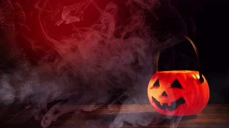Halloween concept - Orange plastic pumpkin lantern on a dark wooden table with smoke around the background, trick or treat, close up. Wideo