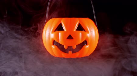 grão : Halloween concept - Moving plastic pumpkin lantern with white smoke around isolated on dark black background, scary and horror mood, close up. Stock Footage