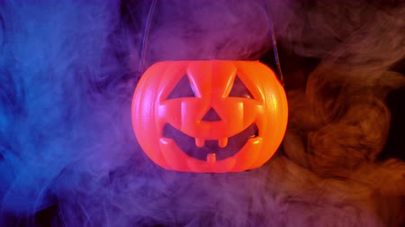 grão : Halloween concept - Moving plastic pumpkin lantern with blue-orange smoke around isolated on dark black background, scary and horror mood, close up.