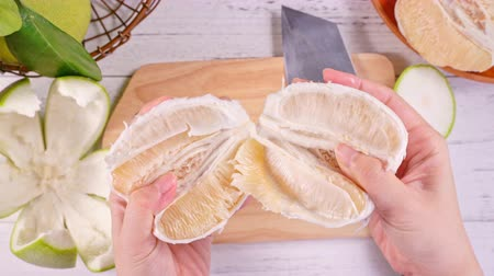 soyulması : Young asian woman is peeling fresh pomelo to eat at home kitchen on bright white wooden table and chopping board, top view, overhead view, lifestyle. Stok Video