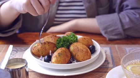 fish ball : Woman in cropped view eating salted cod food, Pasteis de Bacalhau, Bacalao, Bacallao, delicious Portuguese dishes meal in Macau restaurant, lifestyle. Stock Footage