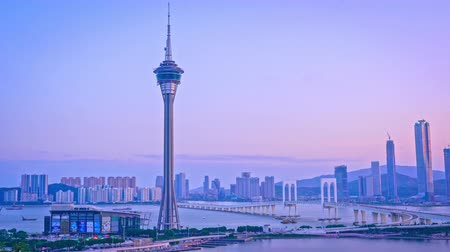 Panorama panning view of Macau (Macao) city skyline during sunset dusk time with Macau tower landmark and Ponte de Sai Van Bridge, concept of busy city.