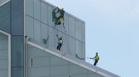 cleaning equipment : Riga, Latvia - September 1, 2016: Unidentified Industrial Climbers - Window washers clean facade of New Building of National Library of Latvia. Stock Footage